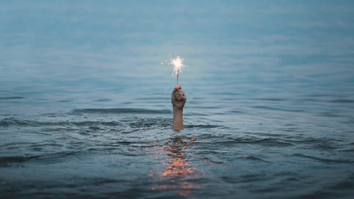 Man in the water holding a sparkle candle