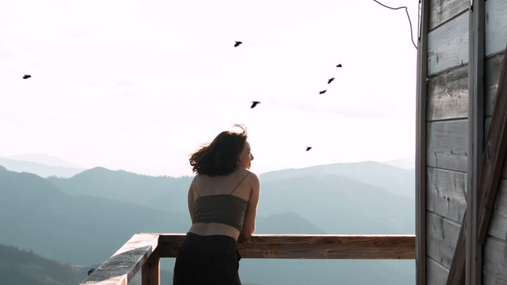 Woman standing at cabin staring the view
